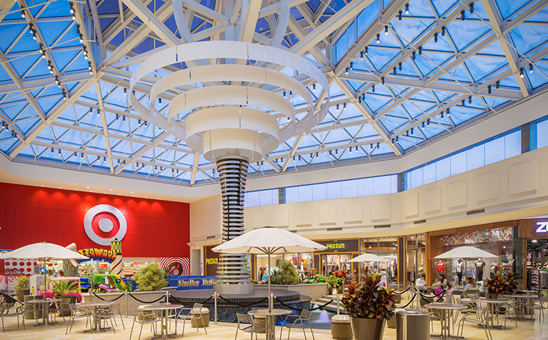 A common area at Christiana Mall has seating for shoppers to relax with an open skylight ceiling.